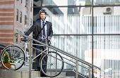 Handsome young businessman with a cycle helmet on head carrying bicycle down steps