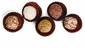 Zigzag of round chocolates wrapped in paper bowl on white background