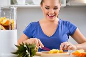Happy young woman preparing healthy food