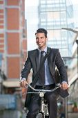 Smiling young businessman riding a bicycle