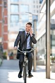 Full length of handsome men go to on riding bicycle by building