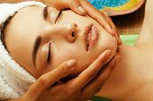 attractive lady getting spa treatment in salon, close up asian hands on face