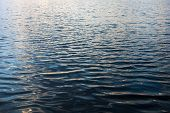 Water Surface With Ripples And Sunrays Reflections