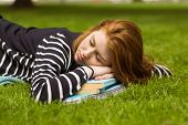 Side view of beautiful young woman lying on grass at the park