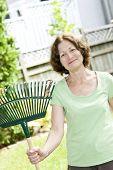 Senior woman smiling holding rake for yard work outside