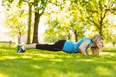 Fit blonde doing push ups in the park on a sunny day