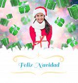 festive brunette holding gift against Christmas greeting card