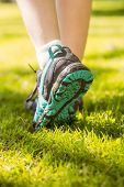 Woman in running shoes stepping on grass on a sunny day
