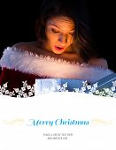 Pretty brunette in santa outfit opening gift against border