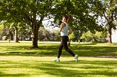 Side view of healthy and beautiful young woman jogging in park