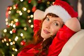 Pretty redhead in santa hat relaxing on the couch at home in the living room