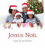Family holding Christmas presents against joyeux noel