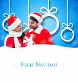 festive young couple holding gift against Christmas greeting card