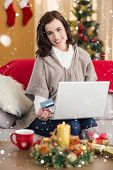 Smiling brunette shopping online with laptop at christmas against snow falling