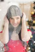 Portrait of a pretty brunette in grey hat against snow falling