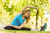 Fit blonde stretching in the park on a sunny day