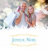 happy couple with shopping bags and credit card against Christmas greeting card