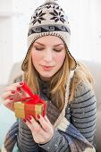 Pretty woman sitting on a couch while opening a gift box against snow falling