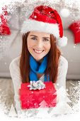 Festive redhead smiling at camera holding gift against christmas theme frame in silver