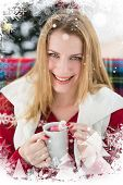 Smiling blonde in winter clothes holding mug against christmas theme frame in silver