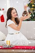 Happy brunette holding baby shoes at christmas against snow falling