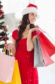 Brunette in red dress holding shopping bags against snow falling