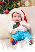 Cute baby boy on couch at christmas against snow falling