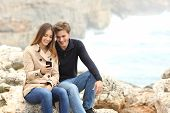 Couple Sharing A Smart Phone On The Beach On Holidays