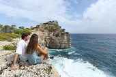 Couple Sitting In A Cliff Watching Ocean Landscape