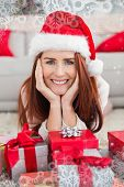 Festive redhead smiling at camera holding gift against snowflake frame