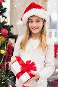 Festive little girl holding a gift against snow falling