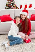 Festive mother and daughter opening a christmas gift against twinkling stars