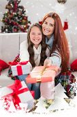 Festive mother and daughter wrapped in blanket with gifts against snow falling