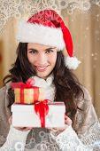 Festive brunette in santa hat holding gifts against snowflake frame