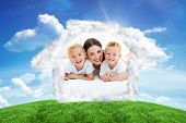Laughing children playing with their mother lying on a bed against green hill under blue sky