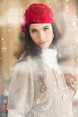 Portrait of a attractive brunette with red hat against snow falling