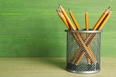 Pencils in metal holder on wooden table and green wooden background