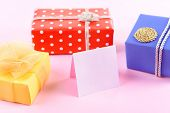 Colorful boxes with greeting card on pink background