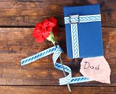 Happy Father's Day with gift box, ribbon, red carnation and greeting card on wooden background