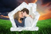 Hugging and kissing couple against green field under orange sky