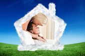 Woman kissing her fiance on the forehead against green field under blue sky