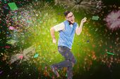 Geeky hipster dancing and smiling against colourful fireworks exploding on black background