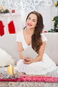 Smiling brunette on the couch reading letter at christmas against snowflake frame