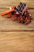 Chocolate with cinnamon and anise on wooden background