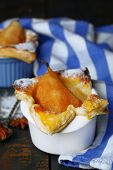 Small pear pies in cups, on wooden table