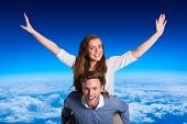 Smiling young man carrying woman against blue sky over clouds at high altitude