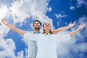 Cute couple standing with arms out against bright blue sky with clouds