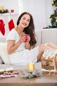 Smiling brunette holding a mug of hot drink against snow falling