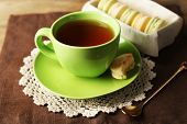 Cup of tea with colorful macarons on wooden background