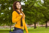 Portrait of smiling female college student with bag in the park